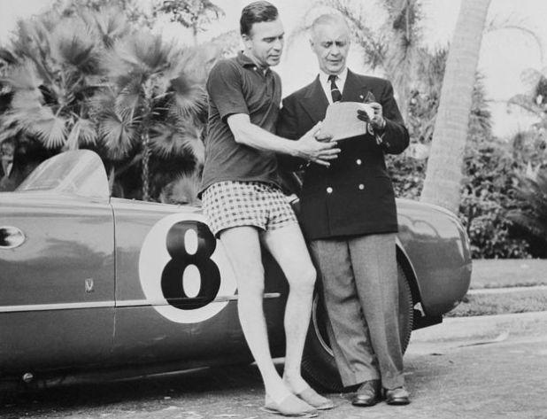Porfirio Rubirosa junto a un auto de carrera.