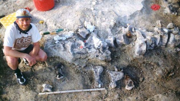 Pesquisador da Universidade do Kansas ao lado de ossos de pé do braquiossauro em escavação no ano de 1998