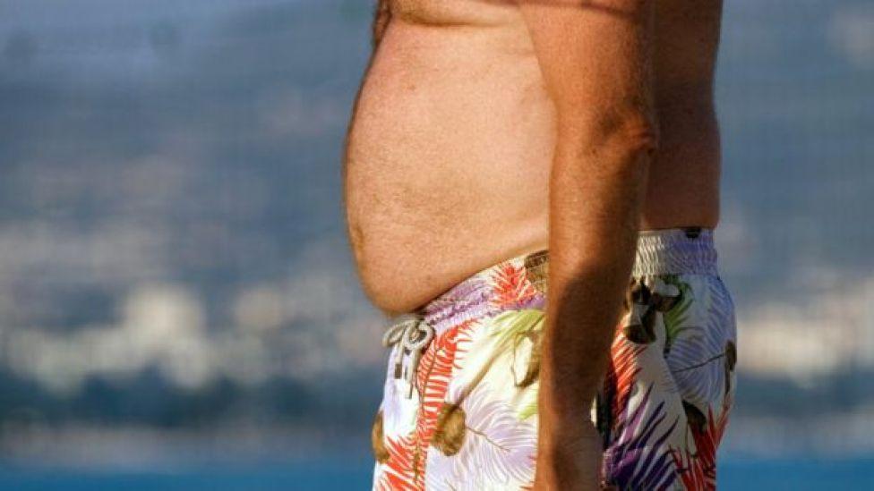 Homem com muita gordura abdominal de bermuda na praia