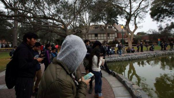 Jóvenes mirando sus celulares en un parque frente a una laguna