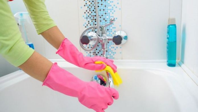 Una personan limpiando una bañera