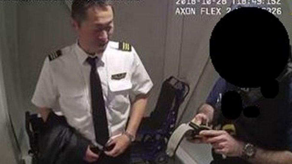 監視カメラ映像は、呼気検査で規定違反値のアルコールが検出され、実川副操縦士が逮捕される様子を映している