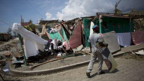 Un hombre carga una pancarta electoral en Les Anglais, Haití, después del paso del huracán Matthew.