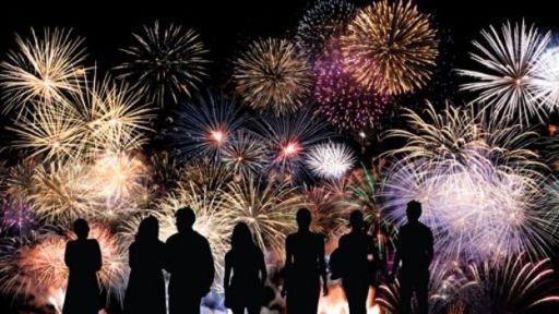 Una fila de personas viendo fuegos artificiales