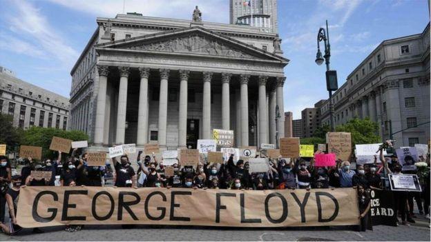 متظاهرون يقفون خلف لافتة ضخمة مكتوب عليها جورج فلويد
