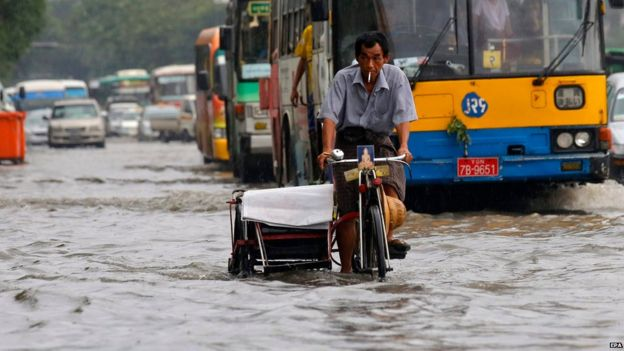 Myanmar man rides a trishaw through a flooded road at downtown area of Yangon, Myanmar, 31 July 2015.