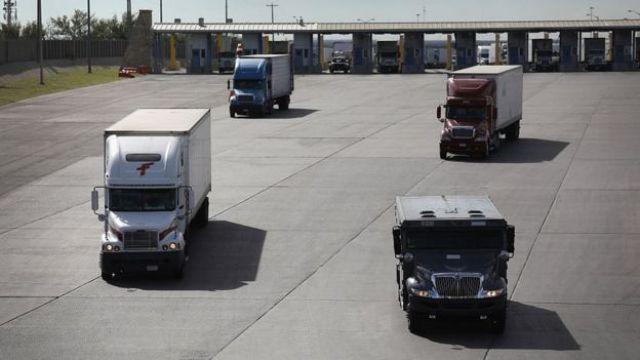 Camiones de carga cruzan la frontera entre México y Estados Unidos.
