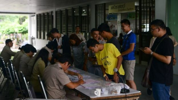Voters check their names on registration lists as they arrive at a polling station in Bangkok. Photo: 7 August 2016