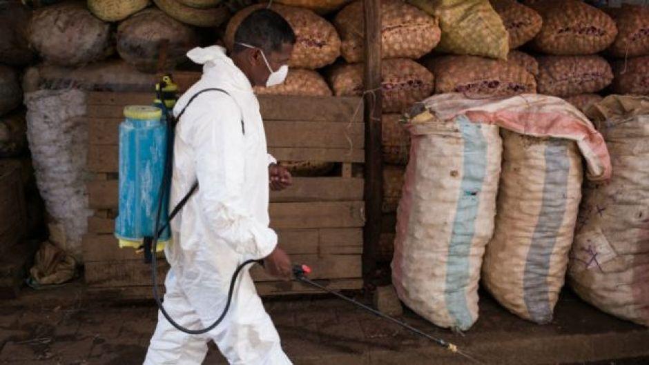Hombre con traje protector desinfectando en Madagascar.
