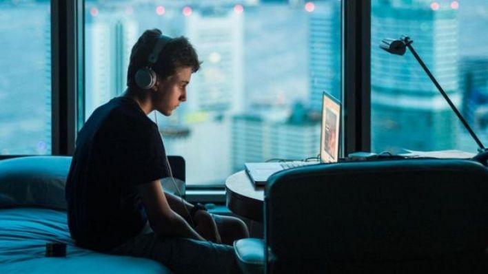 صبي يشاهد جهاز الكمبيوتر المحمول أثناء الليل