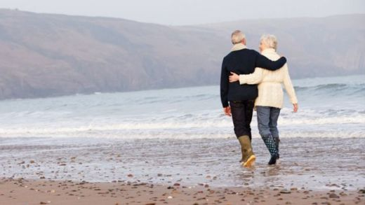 retired couple walk on a beach