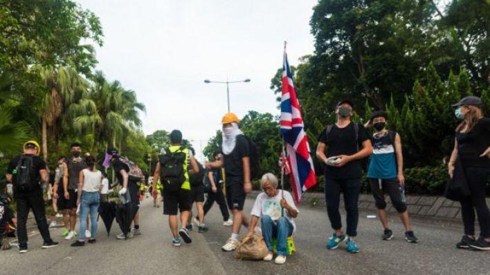 متظاهرة تعيش في شنزن تحمل علم بريطانيا في شيونغ شوي في هونغ كونغ، الصين، في 13 يوليو/تموز 2020