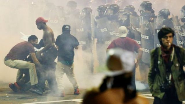 People manoeuvre amongst tear gas in Charlotte, North Carolina during a protest on 21 September