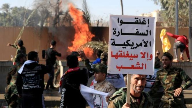 "A man holds up a sign saying ""Close the American embassy or people will close it"" as protesters set fire to the wall of the US embassy compound in Baghdad, Iraq (31 December 2019)"