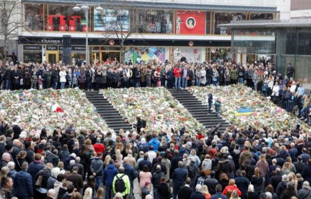 People observe a minute of silence at noon on Sergels Torg to remember the victims of Friday