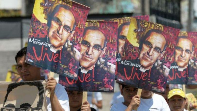 """Fieis com cartazes do monsenhor Arnulfo Romero em que se lê """"Monsenhor vive!"""""""