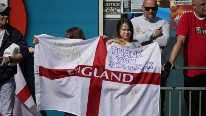 Two youngsters hold up an England flag with messages celebrating Jack Charlton