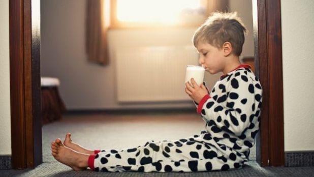 Un niño en pijamas tomando un vaso de leche