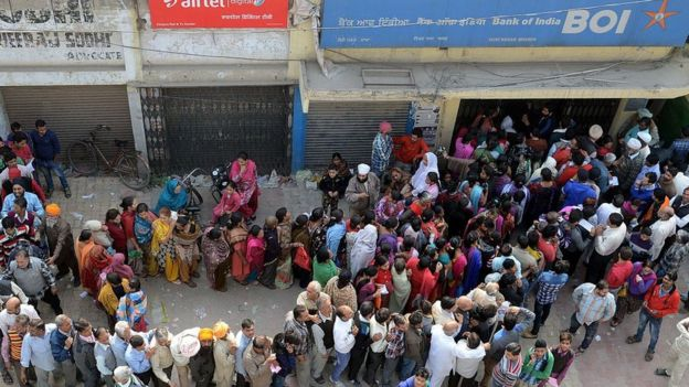Indian people queue outside a bank as they wait to deposit and exchange 500 and 1000 Rupee notes in Amritsar