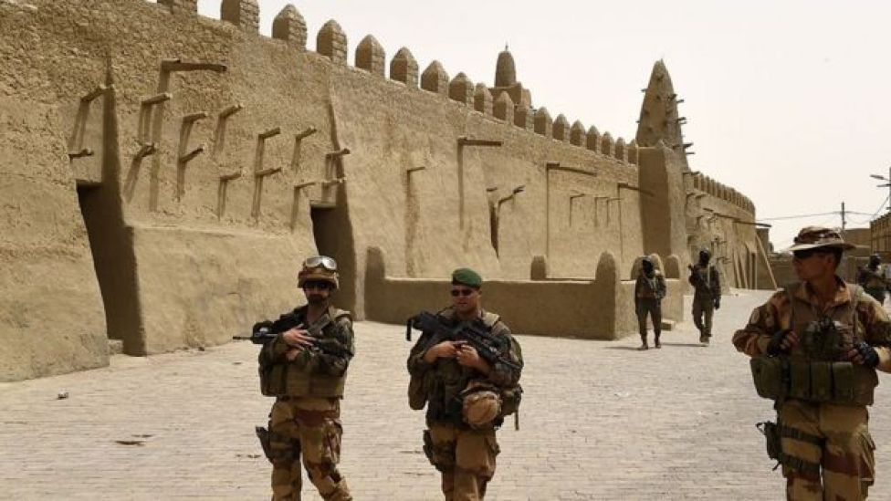 French soldiers of the 93rd Mountain Artillery Regiment and soldiers of the Malian Armed Forces patrol next to the Djingareyber Mosque on June 6, 2015 in Timbuktu
