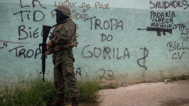 Soldado em frente a muro pichado na Vila Kennedy