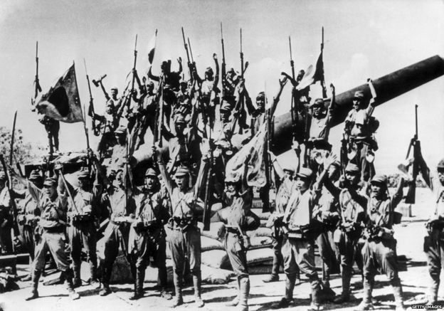 1942: Japanese soldiers celebrate after capturing an American gun emplacement in the Bataan province of the Philippines