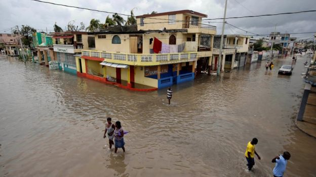 People walk in a flooded area after Hurricane Matthew in Les Cayes