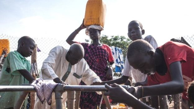 A woman carrying a bucket of water on her head looks on as refugees gather water at the Tomping Internally Displaced Persons (IDP) camp in Juba on July 2, 2014.