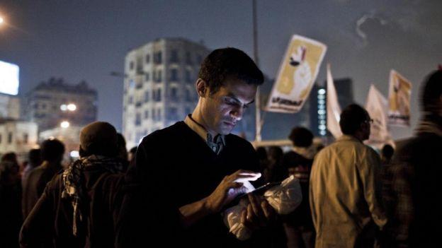 Un joven mira su teléfono inteligente durante unas protestas de la Primavera Árabe