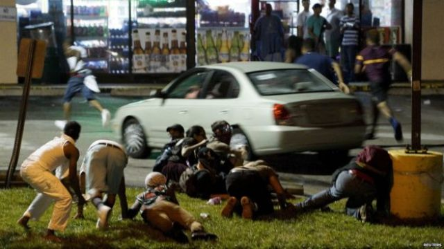 Protesters run to take cover after shots were fired in a police-officer involved shooting in Ferguson, Missouri August 9, 2015.