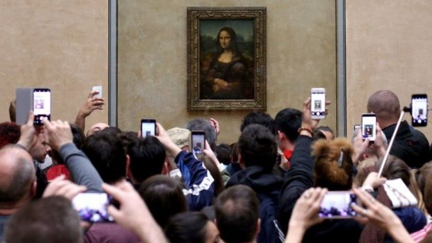 Visitantes toman fotos de la Mona Lisa de Leonardo Da Vinci, en el Museo del Louvre en París.