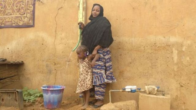 Woman and child filling bucket with water