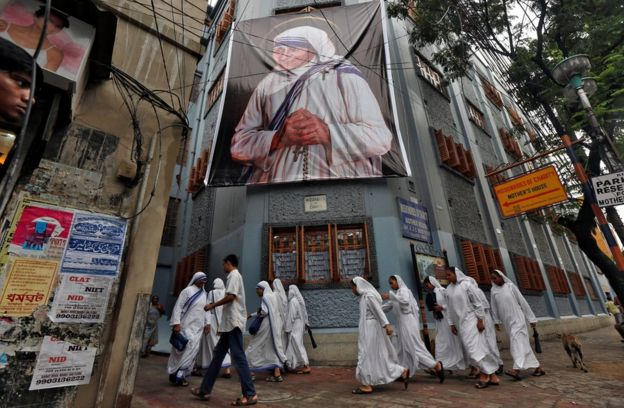 Nuns belonging to the global Missionaries of Charity, walk past a large banner of Mother Teresa ahead of her canonisation ceremony, in Kolkata, India