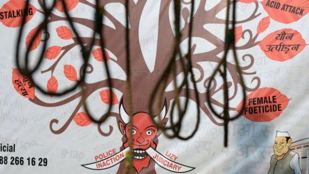 Varias horcas para convictos por violación cuelgan y detrás hay una pancarta con un dibujo de un árbol que en sus ramas lleva las palabras