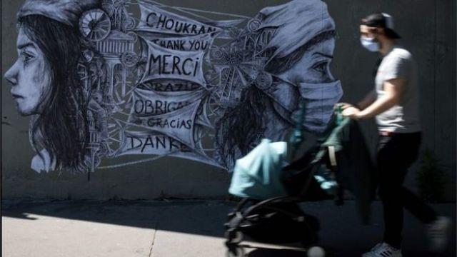 Homem caminha de máscara e com carrinho de bebê diante de mural na França