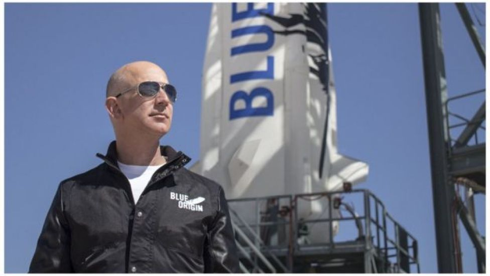 """This April 24, 2015 handout photograph obtained courtesy of Blue Origin shows Jeff Bezos, founder of Blue Origin, at New Shepard""""s West Texas launch facility before the rocket""""s maiden voyage."""