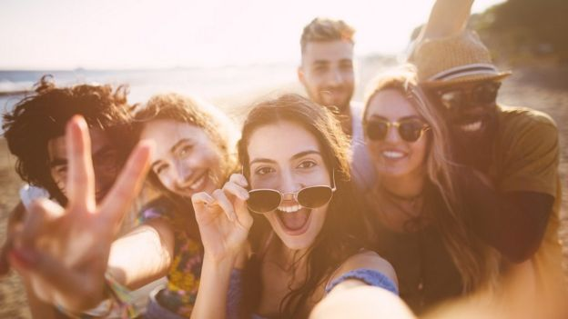 مجموعة من الأصدقاء يلتقطون صور سيلفي على الشاطئ في أجازة الصيف