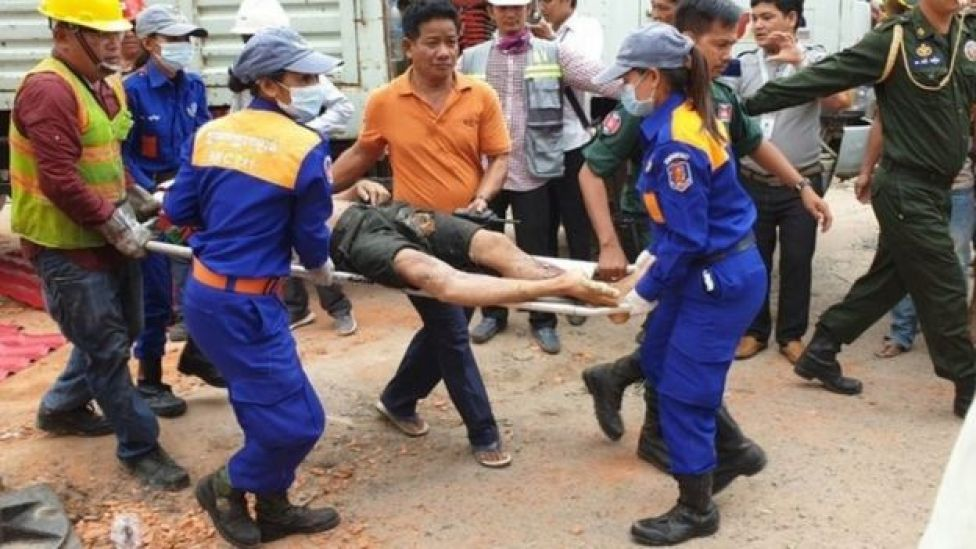 A Cambodian rescue team carries a wounded worker from the building
