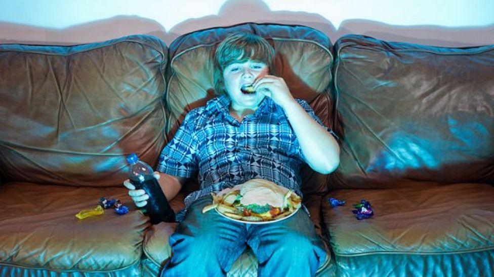 Niño comiendo un plato grande de comida sentado frente a la televisión