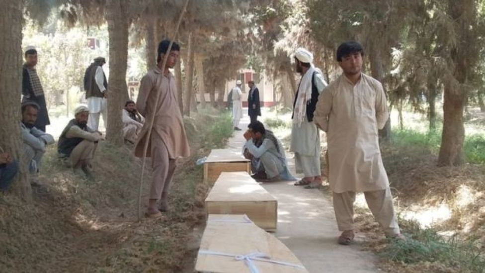 Relatives stand by side of three wooden coffins on a road
