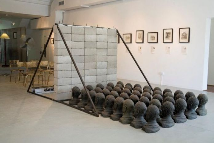 An art installation featuring casts of heads, a brick wall, and chair among other objects