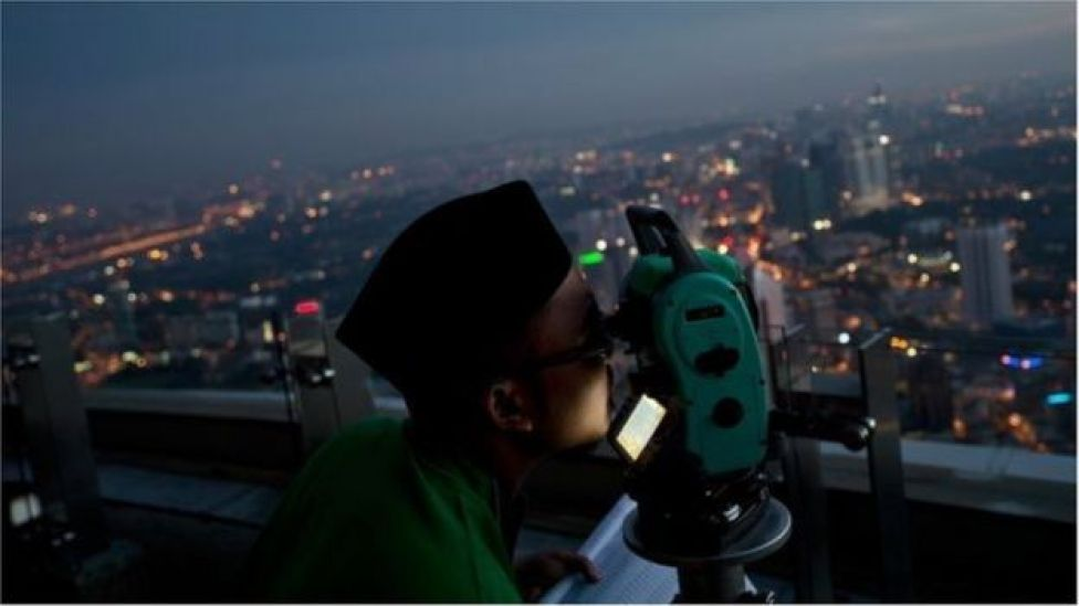 A Malaysian Muslim is trying to see Eid moon in the sky on the telescope