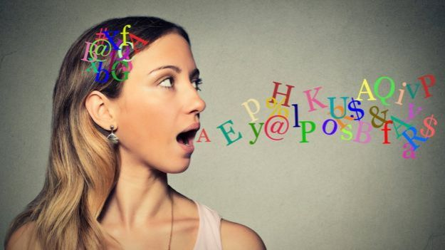 Mujer hablando de letras en cabeza salen de boca abierta.