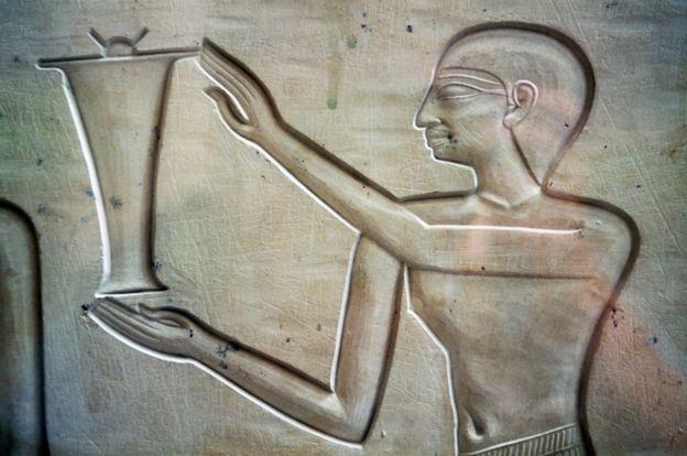 Ilustración de un hombre llevando una jarra de aceite de 2050 a.C.