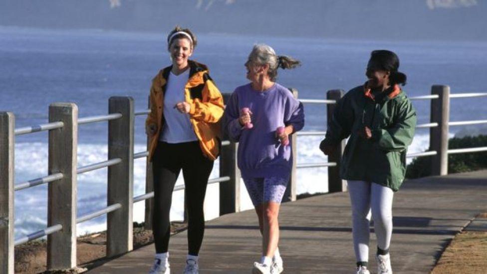 Tres mujeres andando con ritmo rápido por un embarcadero.  Qué tipo de deporte es mejor para estar sano según tu edad  105556394 correr