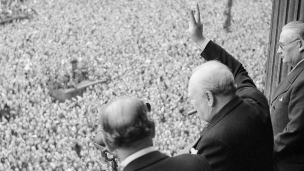 Winston Churchill desde un balcón, saluda a una multitud
