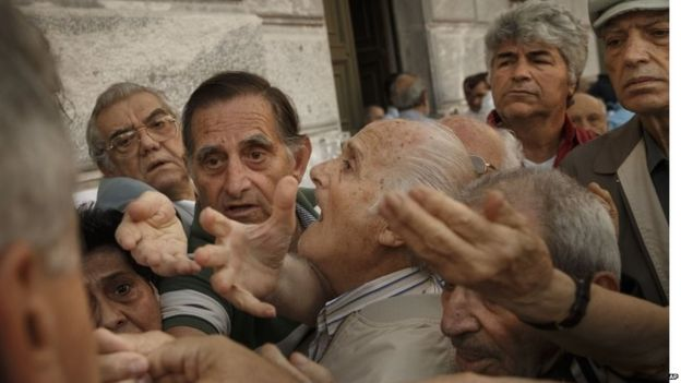 Pensioners try to get a number to enter inside a bank in Athens, Wednesday, July 1, 2015
