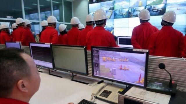 Imagem mostra funcionários da PetroChina em uma sala com diversas telas onde são exibidas etapas da produção