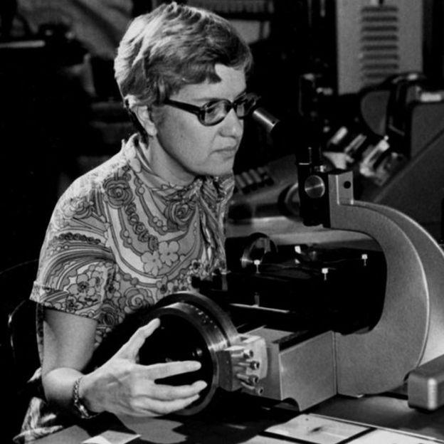 Vera Rubin observa con un microscopio.