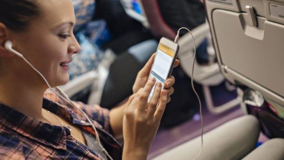 Una mujer maneja su celular dentro de un avión